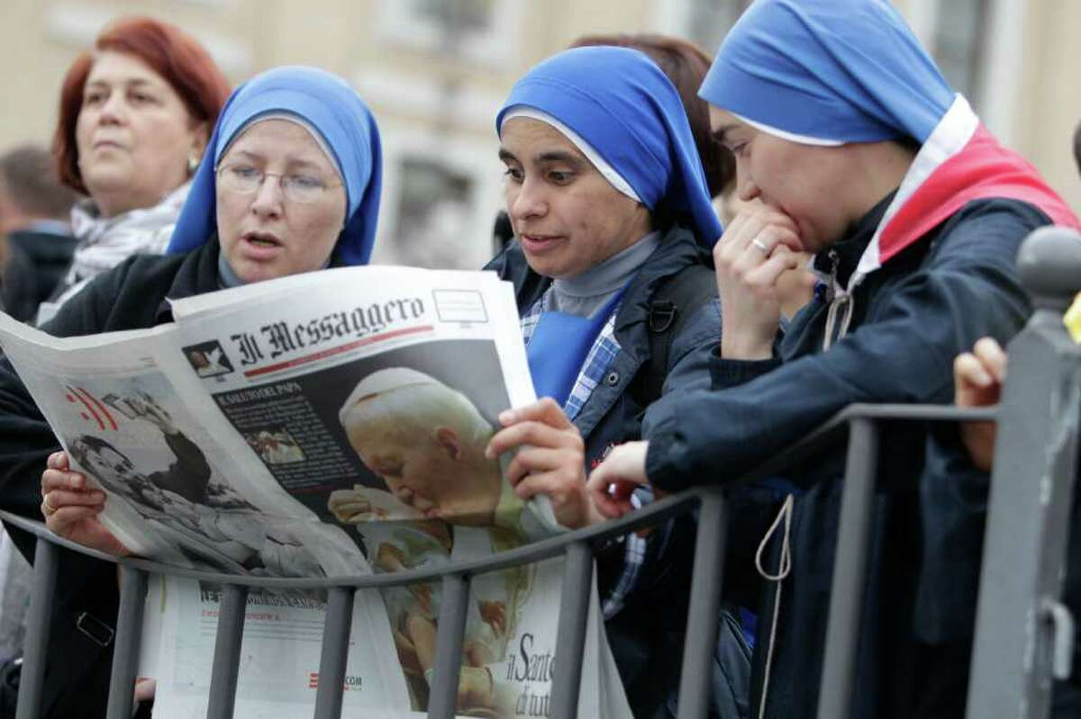 Nuns read a newspaper front-paging a picture of late John Paul II in St. Peter's Square, at the Vatican, Saturday, April 30, 2011, a day before Pope John Paul II's beatification. Tens of thousands of people are converging on Rome for the beatification and many are expected to attend an all-night vigil in Rome's Circus Maximus. (AP Photo/Andrew Medichini)