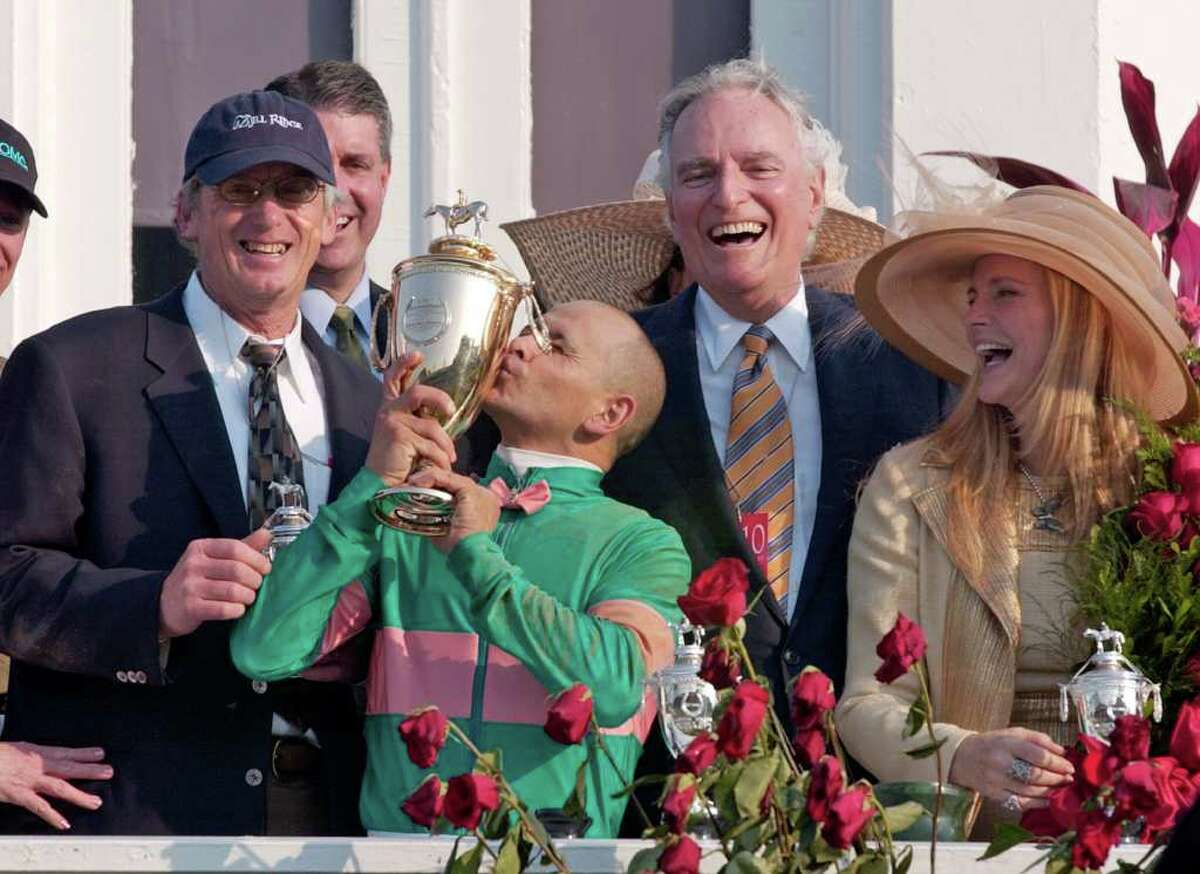 Jockey Mike Smith kisses the trophy as trainer John Shirreffs, left, and owners Jerome and Ann Moss look on after Smith rode Giacomo to win the Kentucky Derby at Churchill Downs, Saturday, May 7, 2005, in Louisville, Ky. (AP Photo/Ed Reinke)