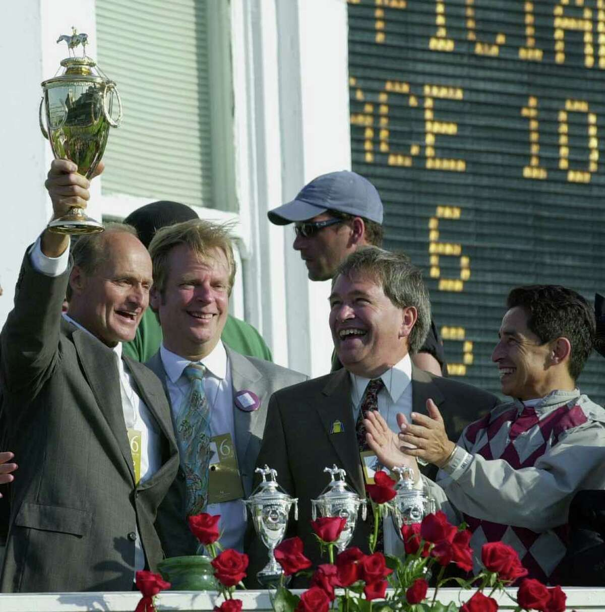 Trainer Barclay Tagg, left, holds the trophy as, from second left, owners David Mahan and Jackson Knowlton and jockey Jose Santos, applaud after Funny Cide won the 129th running of the Kentucky Derby at Churchill Downs, Saturday, May 3, 2003 in Louisville, Ky. (AP Photo/Ed Reinke)