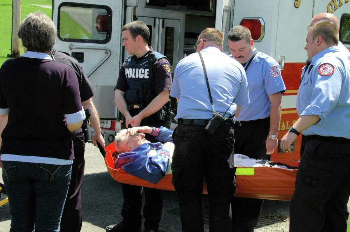 Albert Jolicouer is carried to an ambulance Sunday afternoon by emergency personnel. The 86-year-old was found Sunday in a wooded area near the Diamond Rock Adult Facility on Gurley Avenue. He had been missing from the facility since Saturday. BRIAN HOULE PHOTO