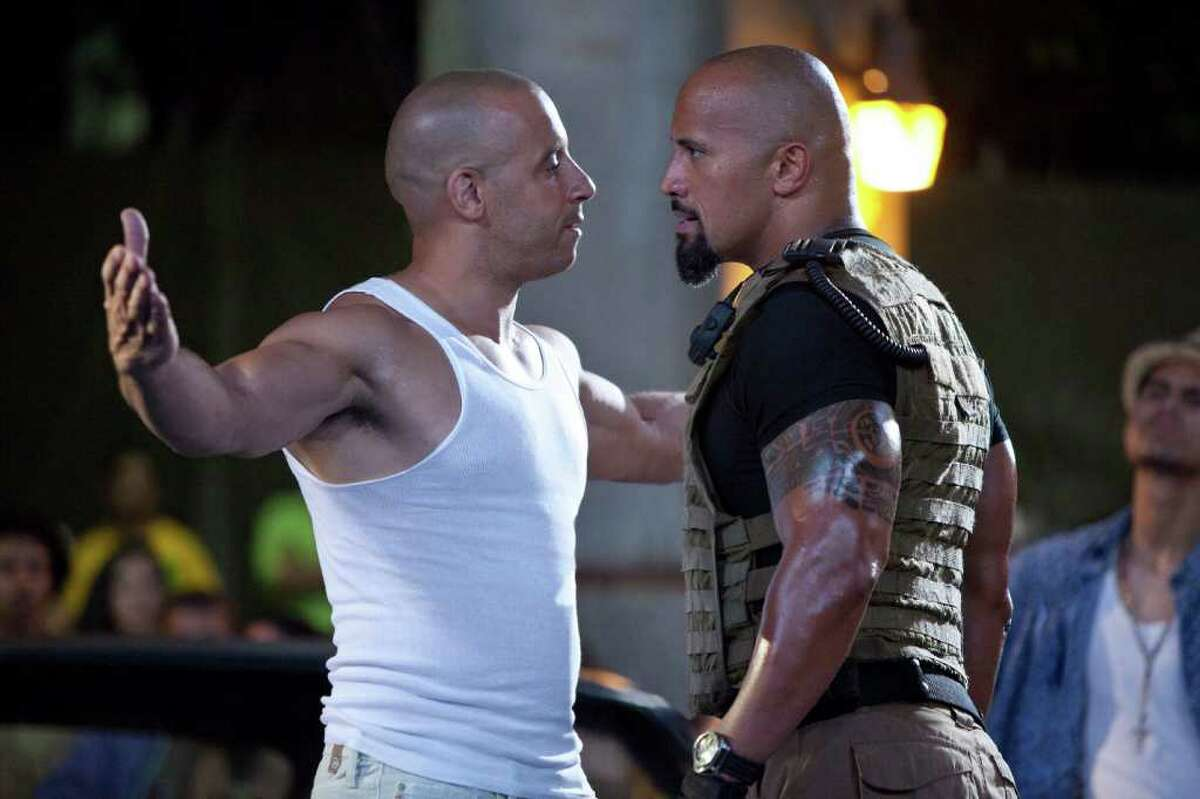 In this film publicity image released by Universal Pictures, Vin Diesel, left, and Dwayne Johnson are shown in a scene from