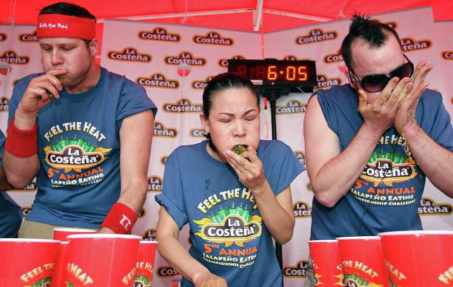"""Erik """"The Red"""" Denmark (from left), Sonya """"The Black Widow"""" Thomas and Patrick """"Deep Dish"""" Bertoletti compete in the 5th Annual La Costeña """"Feel the Heat"""" Jalapeño Eating Championship Challenge Sunday May 1, 2011, at El Mercado. Bertoletti finished in first place, eating 275 jalapeños in eight minutes and won $3000. Thomas finished in second place, eating 224 jalapeños in eight minutes and won $2,000. Denmark finished in third place, eating 121 jalapeños in eight minutes and won $750. Photo: EDWARD A. ORNELAS, Edward A. Ornelas/Express-News / SAN ANTONIO EXPRESS-NEWS (NFS)"""