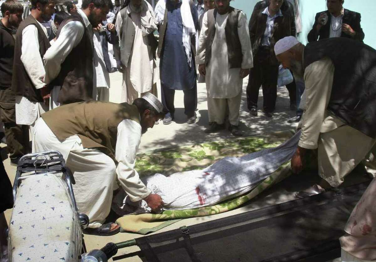 Relatives wrap the body of a civilian, who was killed during a clash of militants with policemen in Ghazni southwest of Kabul, Afghanistan on Sunday, May 1, 2011. Militants staged attacks in two Afghan provinces, killing six people, including a district council member and two policemen on Sunday, the first day of the Taliban's announced spring offensive, said government officials. A gunman opened fire on a checkpoint, in Ghazni province, killing two policemen and wounding a bystander during an hour long battle, provincial police chief Zerawar Zahid said. (AP Photo/Rahmatullah Nikzad)