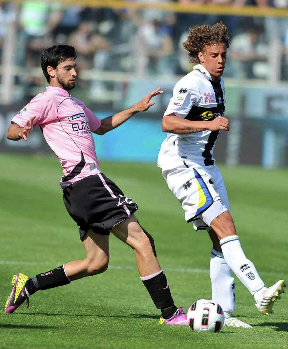 Palermo's Javier Pastore, left, of Argentina, tries to pass Parma Swiss defender Rolf Feltscher during their Serie A soccer match against Parma, at Parma's Tardini stadium, Italy, Sunday, May 1, 2011. Parma won 3-1. (AP Photo/Massimo Morelli,LaPresse) ITALY OUT