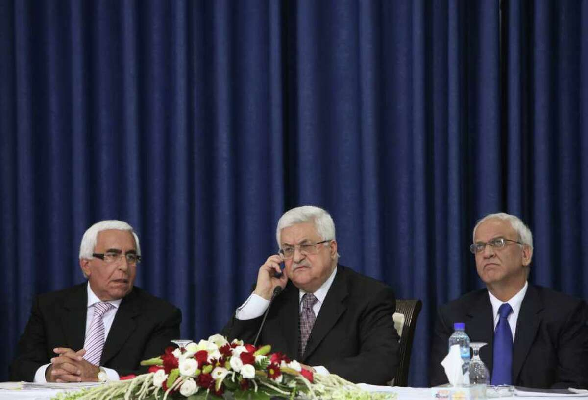 Palestinian President Mahmoud Abbas, center, talks as Palestinian negotiator Saeb Erekat, right, and Moshe Shachal, a member of the Israeli Peace Initiative, listen during a press conference in Ramallah, Thursday, April 28, 2011. Israeli leaders on Thursday rejected the new Palestinian unity deal between the rival Hamas and Fatah factions, saying it could destroy the prospects for peace in the region. (AP Photo/Tara Todras-Whitehill)