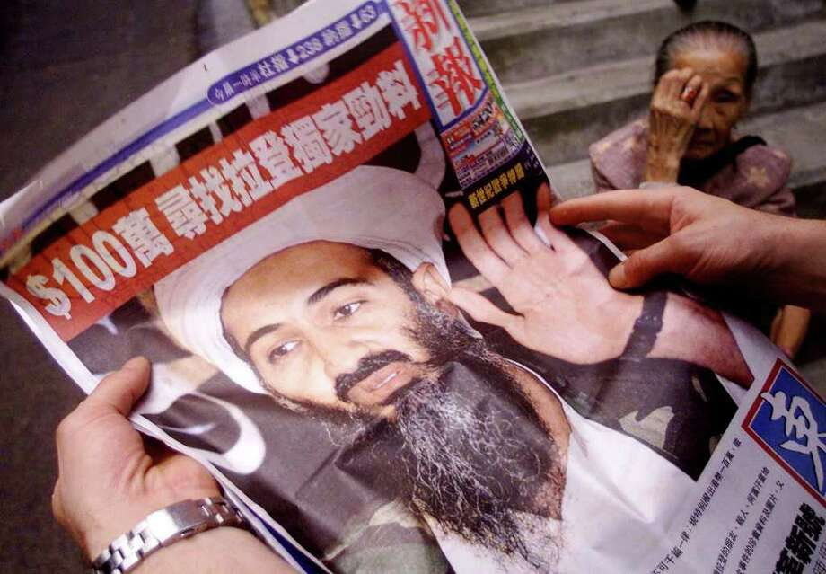 A man looks at an advert splashed across a Hong Kong newspaper offering a one million HK dollar (128,200 USD) reward for any information on suspected Saudi terrorist Osama bin Laden, Sept. 21, 2001.  The ad, placed by the Hong Kong magazine Eastweek, offered the reward for anyone who could provide exclusive information about bin Laden.  The magazine denied the reward was for information that would lead to bin Laden's arrest, saying its stance on the issue was neutral.  AFP PHOTO/Peter PARKS Photo: PETER PARKS, AFP/Getty Images / AFP