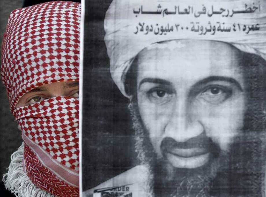 A Palestinian militant from the Islamic Jihad movement displays a portrait of Saudi dissident Osama bin Laden during the funeral of  Palestinian youth Ahmad Yassin in Gaza City, July 2, 2001. Photo: FAYEZ NURELDINE, AFP/Getty Images / AFP