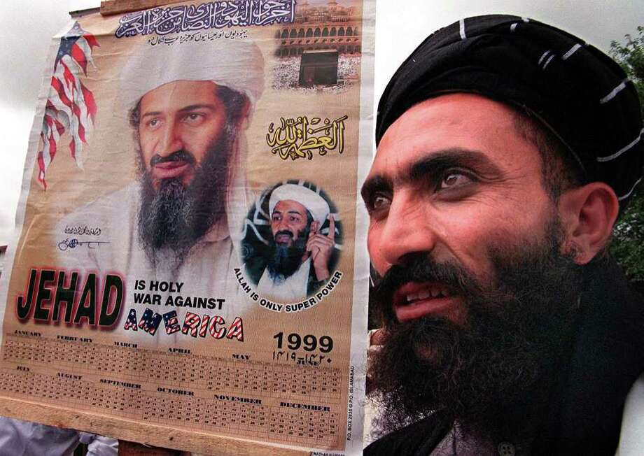 A religious protester holds a portrait of Saudi dissident Osama bin Laden during a protest rally against the United States, July 30, 1999 in Islamabad. Photo: SAEED KHAN, AFP/Getty Images / AFP