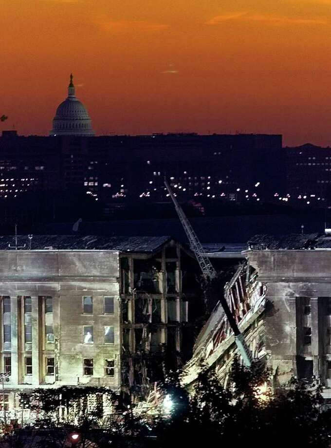 The sky glows orange as the sun rises over the damaged side of the Pentagon with the U.S. Capitol behind in Washington, Sept. 13, 2001.  A hijacked airplane crashed into the Pentagon on Sept. 11, 2001, causing extensive damage. Photo: LUKE FRAZZA, AFP/Getty Images / AFP