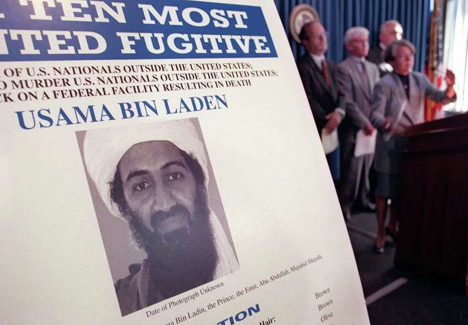 Osama Bin Laden is seen on a poster at the US Justice Department press conference announcing the arrest and arraignment of Khalfan Khamis Mohamed Oct. 8, 1999 in New York. Mohamed is accused of being a member of Bin Laden's terrorist organization and a participant in the Aug. 7, 1998 bombings of the US embassies in Dar es Salaam, Tanzania and Nairobi, Kenya. Mohamed was apprehended several days ago in South Africa. AFP PHOTO  Doug KANTER Photo: DOUG KANTER, AFP/Getty Images / AFP