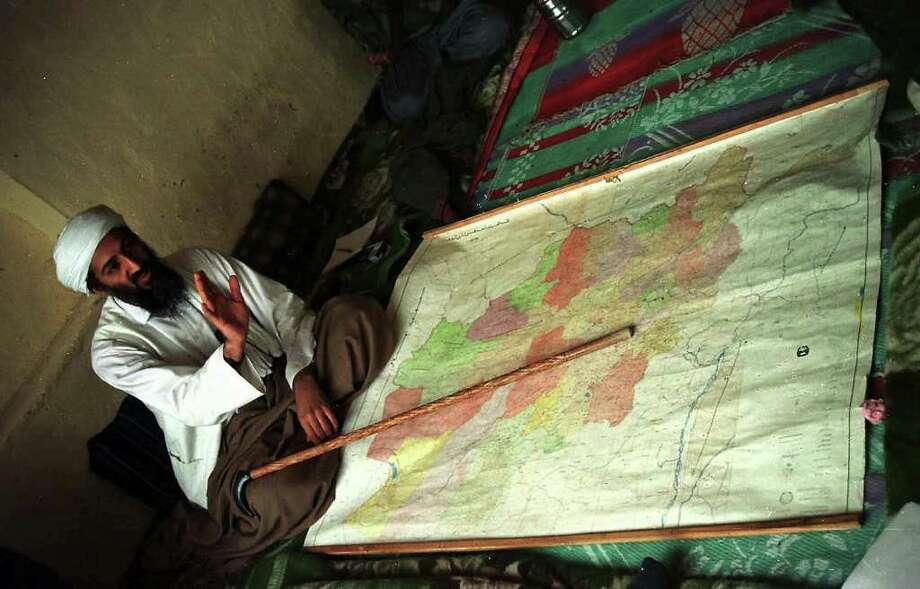 Exiled Saudi dissident Osama bin Laden is seen in this April 1998 file photo sitting behind a map of Afghanistan in an undisclosed region of the country.  (AP Photo) Photo: Associated Press / AP