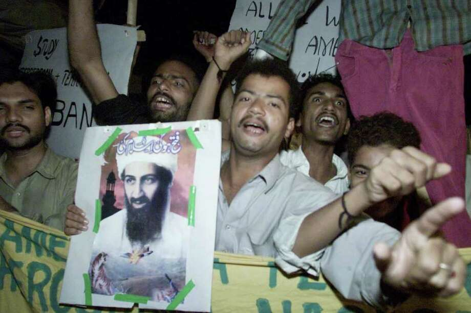 A small group of Pakistani supporters of the ruling Taliban in Afghanistan display a portrait of terrorist suspect Osama bin Laden as they stage a protest rally in Karachi, Pakistan, soon after the U.S.-led coalition attacked targets in Afghanistan late Sunday, Oct. 7, 2001. AP Photo/Zia Mazhar) Photo: ZIA MAZHAR, Associated Press / AP