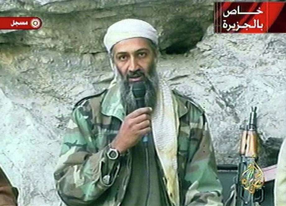 "Osama bin Laden is seen at an undisclosed location in this television image broadcast Sunday, Oct. 7, 2001. Bin Laden praised God for the Sept. 11 terrorist attacks and swore America ""will never dream of security"" until ""the infidel's armies leave the land of Muhammad,"" in a videotaped statement aired after the strike launched Sunday by the United States and Britain in Afghanistan. Graphic at top right reads ""Exclusive to Al-Jazeera."" At bottom right is the station's logo which reads ""Al-Jazeera."" At top left is ""recorded."" (AP Photo/Al Jazeera) Photo: Associated Press / AL JAZEERA"