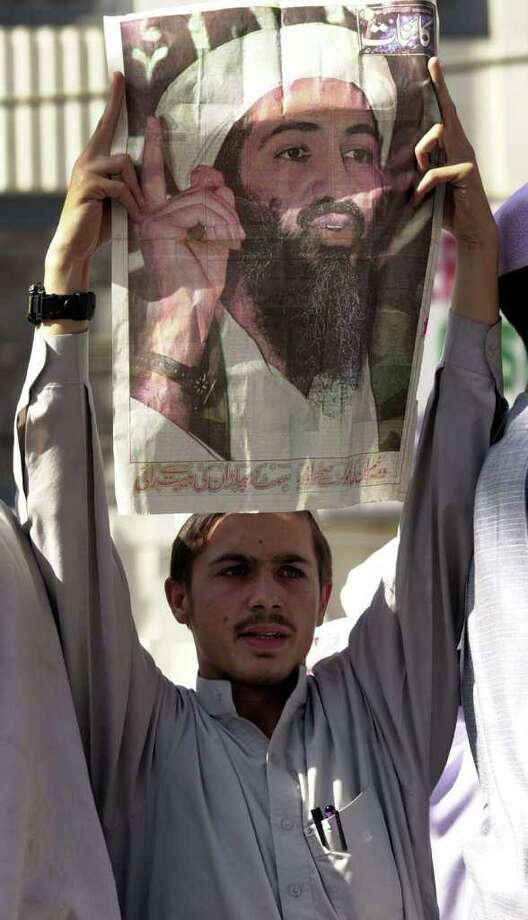 A Pakistani man holds a poster of Osama bin Laden during a rally in support of the Taliban and bin Laden and against the U.S. Friday Oct. 12, 2001 in Peshawar, Pakistan. A few thousand men took part in the event PHOTO BY EDWARD A. ORNELAS/HEARST Photo: EDWARD A. ORNELAS, SAN ANTONIO EXPRESS-NEWS  / SAN ANTONIO EXPRESS-NEWS