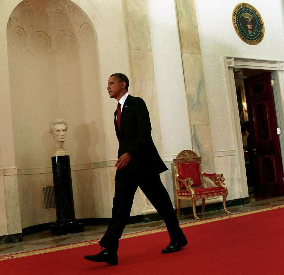 President Barack Obama walks down the Cross Hall on the way to the East Room to make a televised statement on the death of Osama bin Laden from the White House in Washington, Sunday, May 1, 2011. Photo: AP