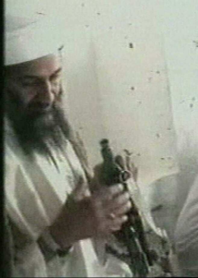This television image released by Qatar's Al-Jazeera television broadcast on Friday Oct. 5, 2001 is said to show the most recent image of Osama bin Laden, left, handling a Kalshnikov rifle at an undisclosed location.  A person familiar with developments said Sunday, May 1, 2011 that bin Laden is dead and the U.S. has the body. Photo: AP