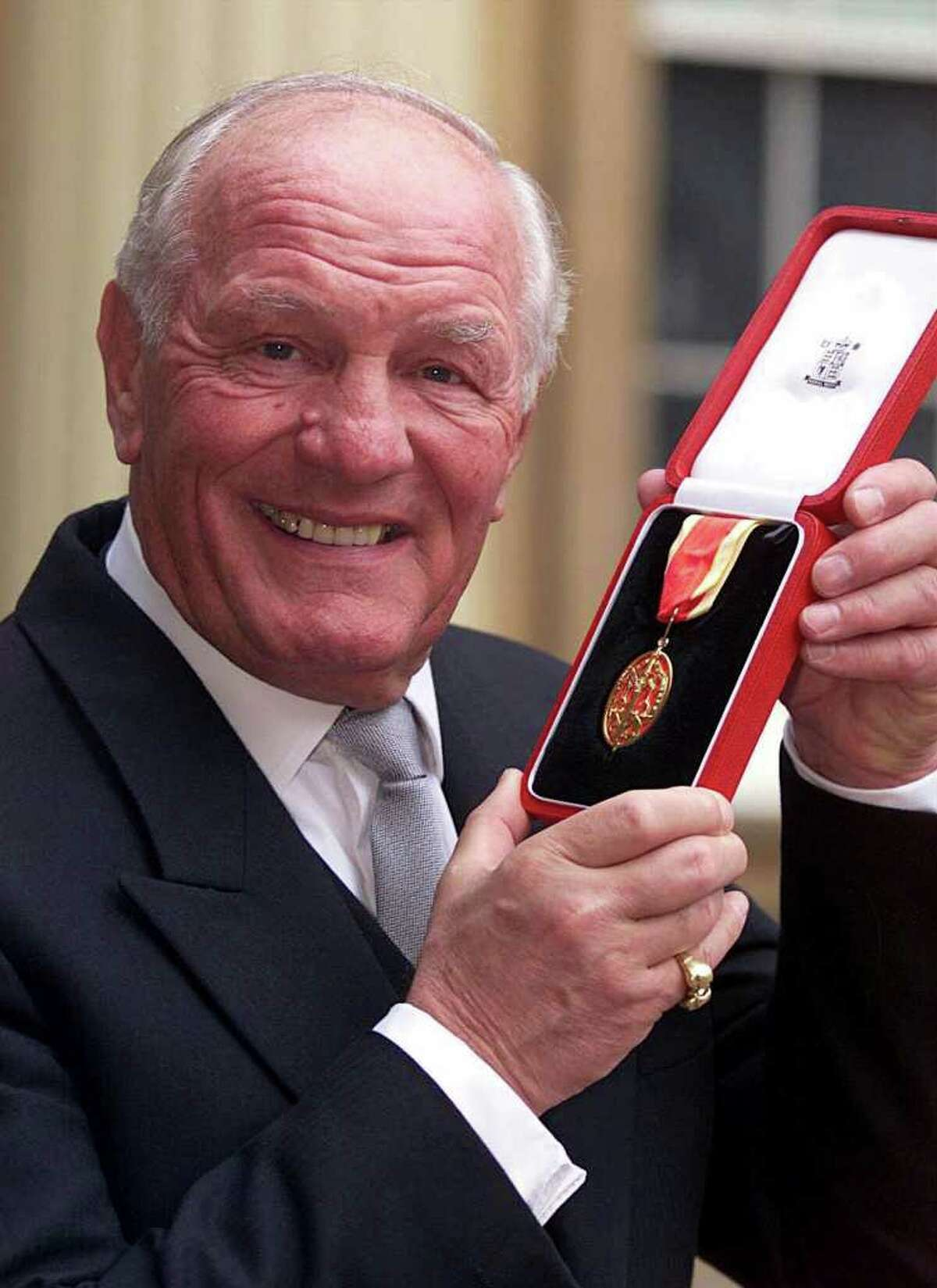 FILE - This Tuesday Feb. 22, 200 photo from files shows former British and European heavyweight boxing champion Sir Henry Cooper after receiving his knighthood at an investiture ceremony at Buckingham Palace in London. Sir Henry has died aged 76, sources told Britain's Press Association Sunday May 1, 2011. He was well known for two famous clashes with Muhammad Ali in the 1960's flooring Ali in the 4th round of a 1963 non-title fight at London's Wembley, though Ali eventually won the fight. He fought Ali again in 1966 but was again beaten. (AP Photo/Richard Pohle, Pool)
