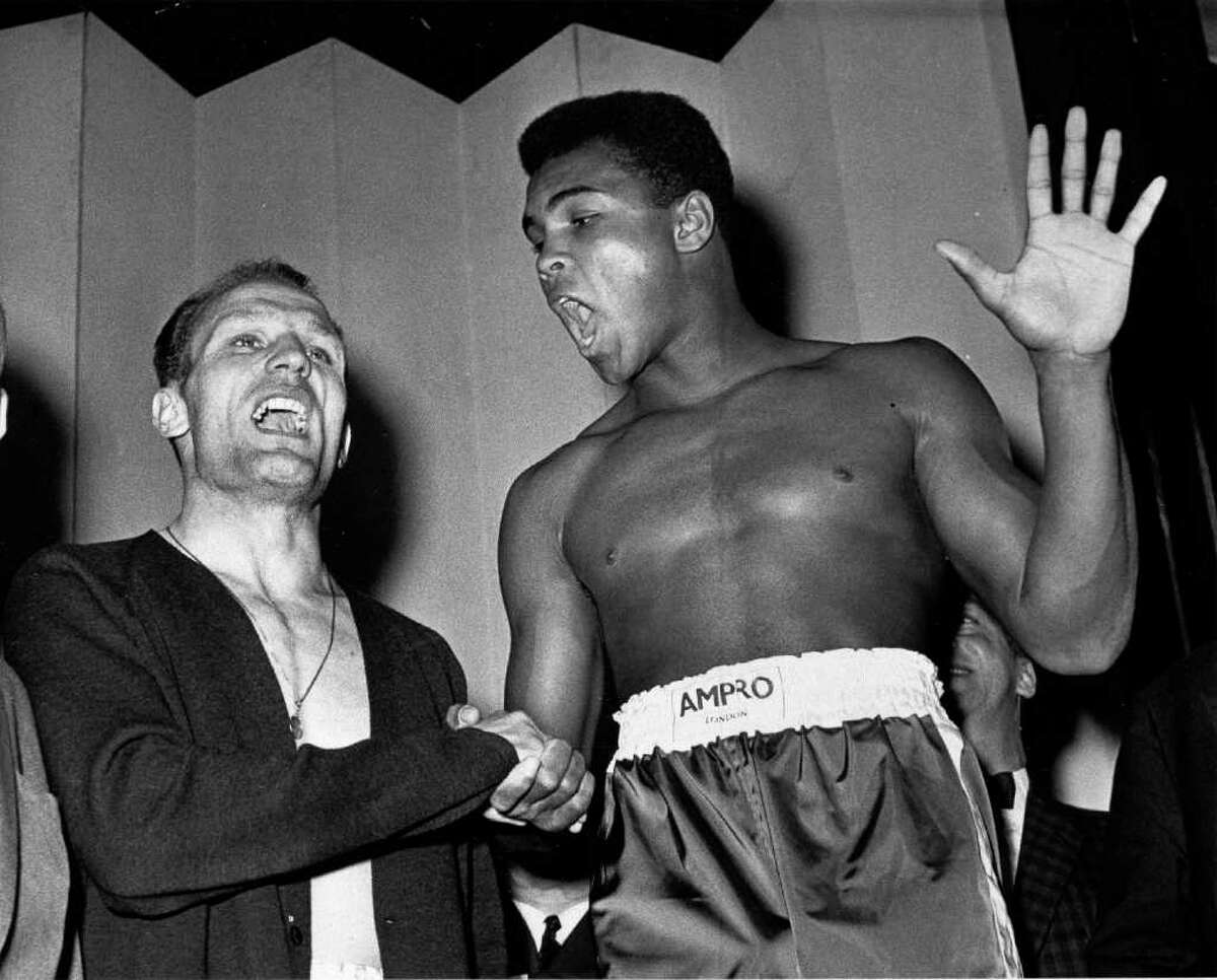 FILE - A June 18, 1963 photo from files showing world famous boxer Muhammad Ali (or Cassius Clay as he was then known), right, and British heavyweight champion Henry Cooper as they seem to be trying to out shout each other at weigh-in in London for their heavyweight fight the same evening. Ali holds up five fingers, the number of rounds he modestly predicts he'll knockout Cooper.Sir Henry has died aged 76, sources told Britain's Press Association Sunday May 1, 2011. He was well known for two famous clashes with Muhammad Ali in the 1960's flooring Ali in the 4th round of a 1963 non-title fight at London's Wembley, though Ali eventually won the fight. He fought Ali again in 1966 but was again beaten. (AP Photo)
