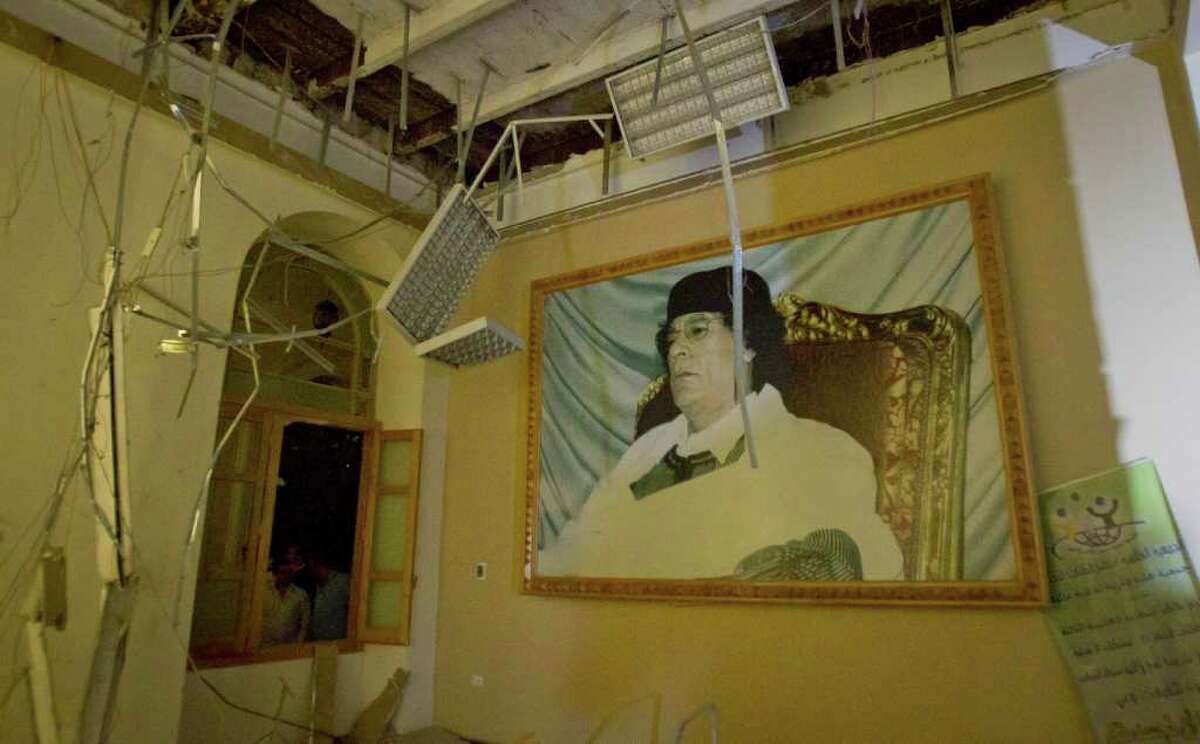 In this photo made on a government organized tour, a portrait of Moammar Gadhafi is seen inside damaged official building following an airstrike in Tripoli, Libya, early Saturday, April 30, 2011.(AP Photo/Darko Bandic)