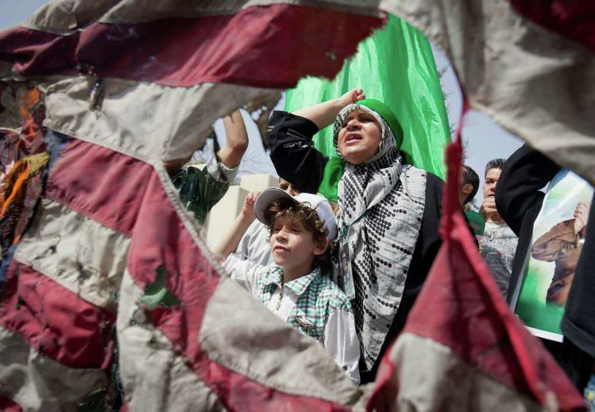 In this photo taken during a government organized tour, seen through a burning US flag, protesters chant anti-US slogans in front of the Gadhafi family compound in a residential area of Tripoli, Libya, Sunday, May 1, 2011. Libyan leader Moammar Gadhafi escaped a NATO missile strike in Tripoli that killed one of his sons and three young grandchildren, a government spokesman said early Sunday. (AP Photo/Darko Bandic)