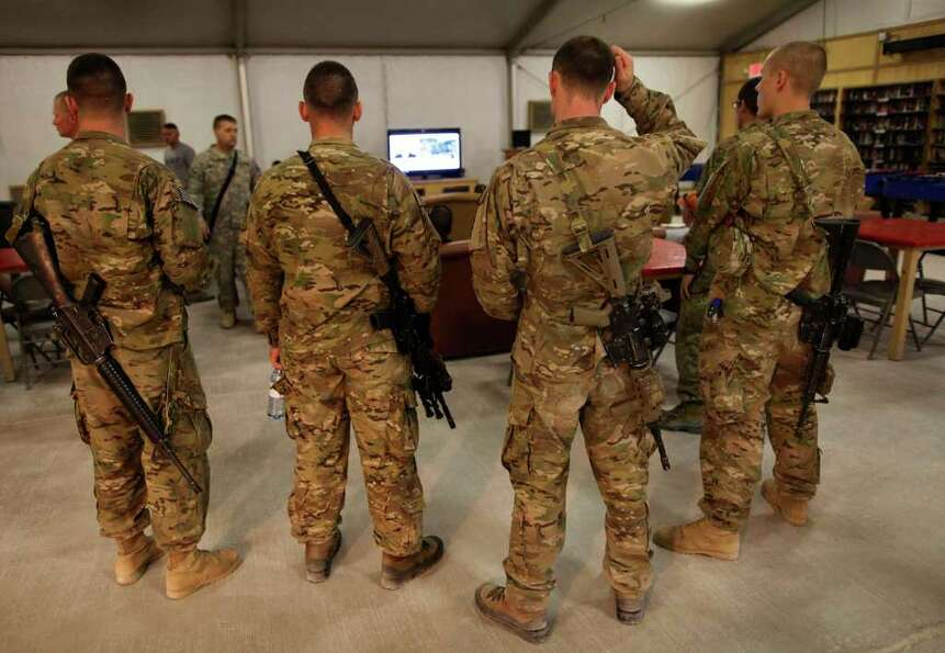 United States military troops watch breaking news on the announcement by President Barack Obama that