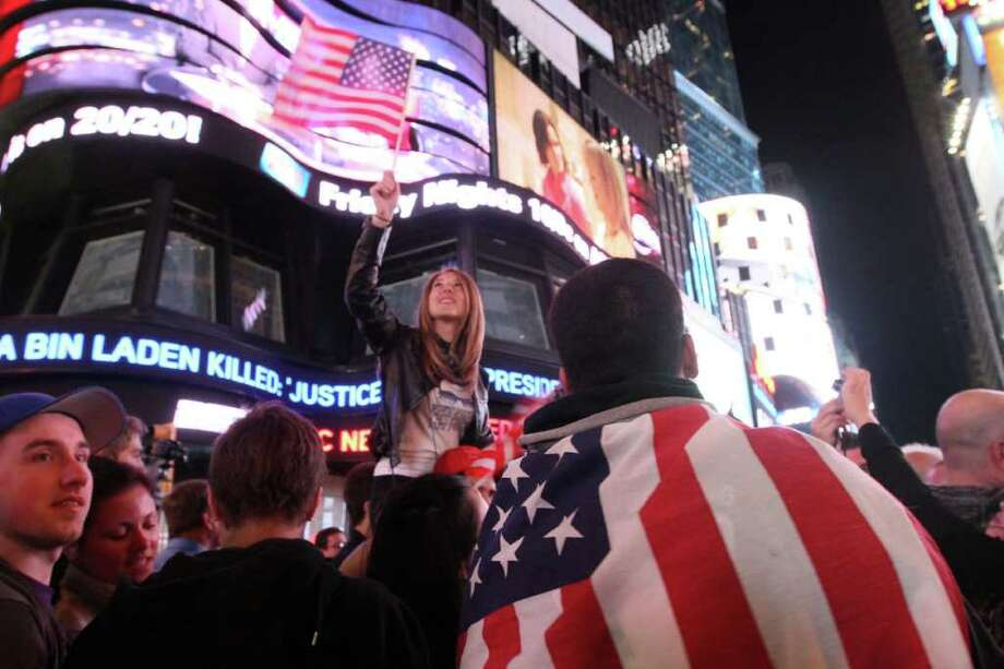 Draped in the American flag, Pedro Valerio, of Elizabeth, N.J., right, and others in New York's Times Square react to the news of Osama Bin Laden's death early Monday morning May 2, 2011. Photo: AP