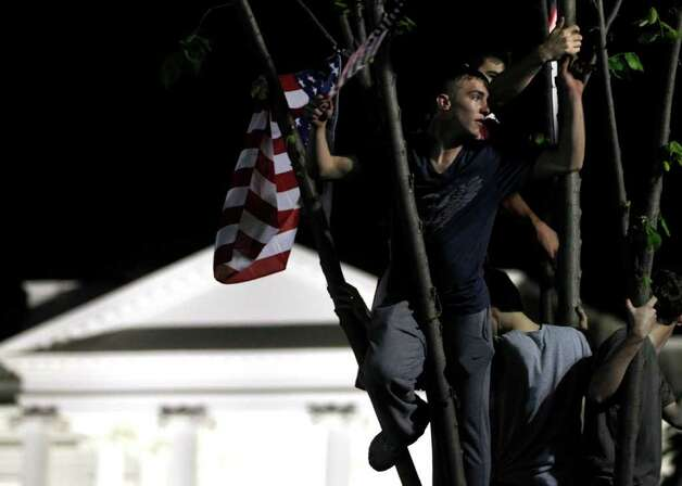 Climbing trees, crowds celebrate on Pennsylvania Avenue in front of the White House in Washington, early Monday, May 2, 2011, after President Barack Obama announced that Osama bin Laden had been killed. Photo: AP
