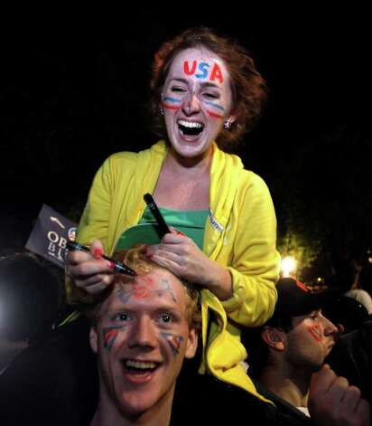 "Analisa Cotter, 20, writes ""USA"" on Paul Deasey's forehead as crowds celebrate on Pennsylvania Avenue in front of the White House in Washington, early Monday, May 2, 2011, after President Barack Obama announced that Osama bin Laden had been killed. Photo: AP"
