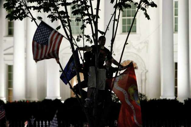 A man waves an American flag and the Marine Corps flag from a tree in front of the White House people early Monday, May 2, 20111, across the street from the White House in Washington, as people gather to cheer the United States after it was announced that Osama bin Laden has been killed. Photo: AP