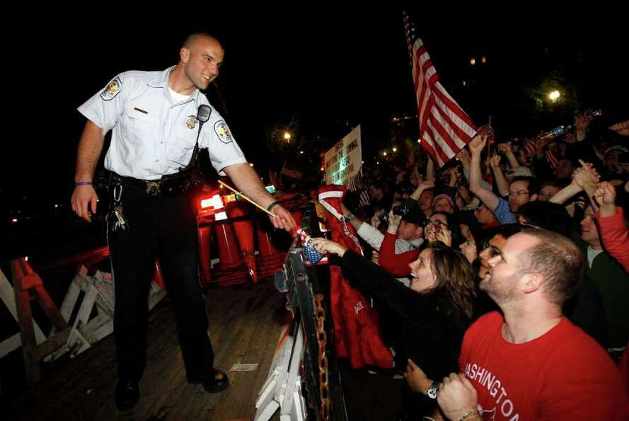 A U.S. Park Police officer is handed a flag as crowds celebrate on Pennsylvania Avenue in front of t