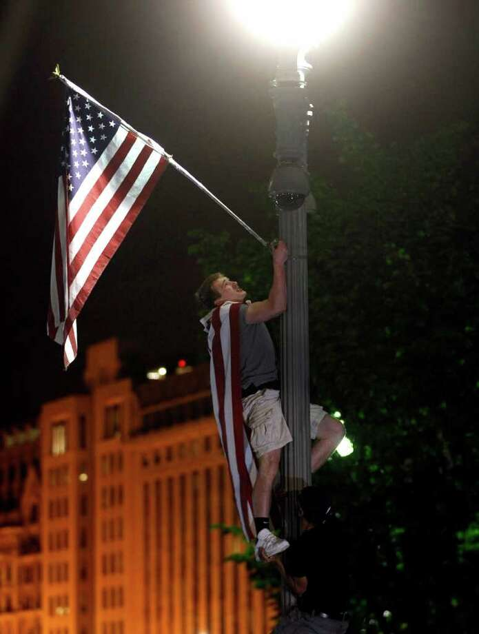 An unidentified celebrant climbs a light pole as crowds celebrate on Pennsylvania Avenue in front of the White House in Washington, early Monday, May 2, 2011, after President Barack Obama announced that Osama bin Laden had been killed. Photo: AP