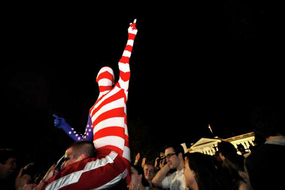 "A man who said he was dressed as ""Captain America,"" cheers early Monday, May 2, 20111, across the street from the White House in Washington, as people gather to cheer the United States after it was announced that Osama bin Laden has been killed. Photo: AP"