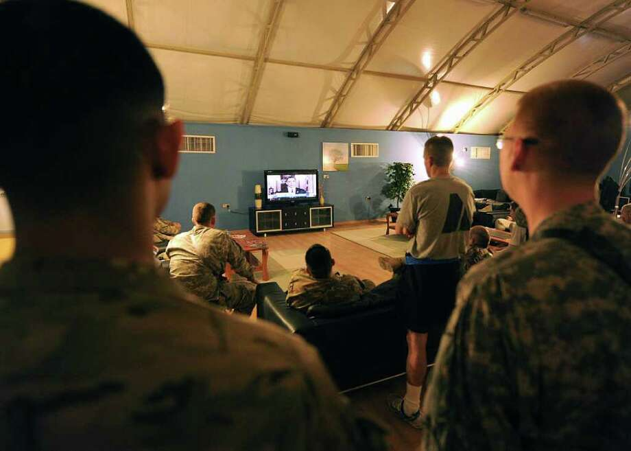 In this image provided by the U.S. Army, service members watch on television President Barack Obama talk about the death of Osama bin Laden inside the USO at Kandahar Airfield, Afghanistan, on Monday, May 2, 2011. Photo: AP