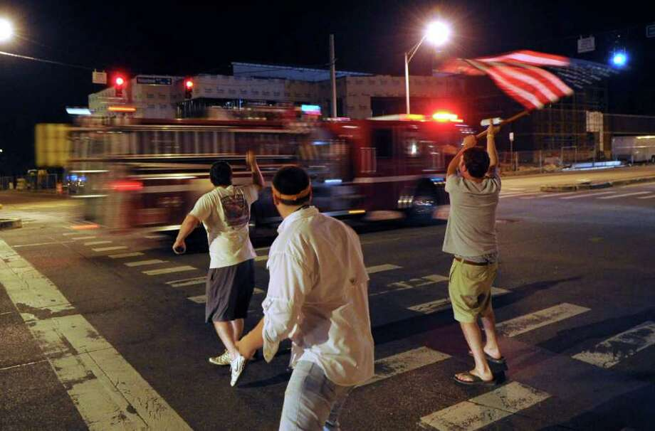 "University of Tennessee students, from left, Josh Hixson, Will Batey and Colin Marcum, cheer as a Knoxville Fire Department fire truck honks its horn while driving down Volunteer Boulevard on campus Sunday, May 1, 2011, in Knoxville, Tenn.  The students were in the process of painting ""The Rock"" with anti-Osama bin Laden sentiments while the KFD unit was responding to a tree fire on fraternity row after President Obama's announcement that the terror leader had been killed in Pakistan. Photo: AP"