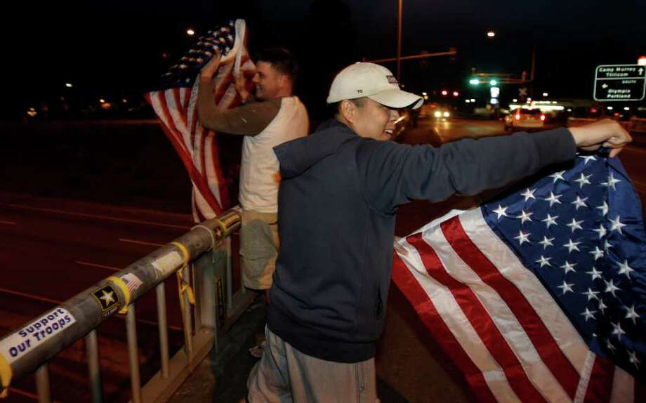 "U.S. Army Staff Sgt. Lemuel Nacionales, right, and Spc. Mark Anderson, left, cheer and wave flags on the ""Freedom Bridge"" just outside Joint Base Lewis-McChord, Sunday, May 1, 2011, near Tacoma, Wash., after they heard the news that Osama Bin Laden had been killed. Photo: AP"