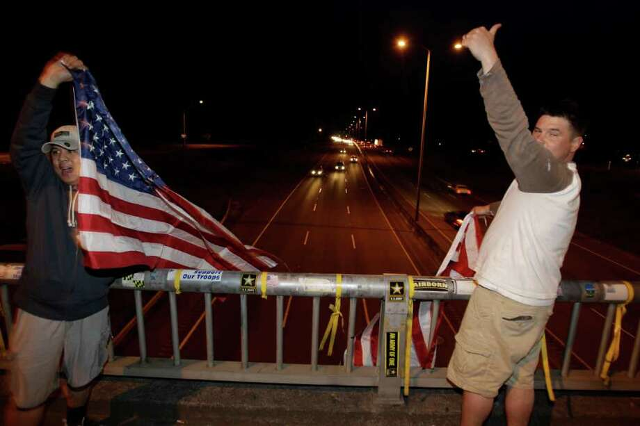 "U.S. Army Staff Sgt. Lemuel Nacionales, left, and Spc. Mark Anderson, right, cheer and wave flags on the ""Freedom Bridge"" just outside Joint Base Lewis-McChord, Sunday, May 1, 2011, near Tacoma, Wash., after they heard the news that Osama Bin Laden had been killed. Photo: AP"