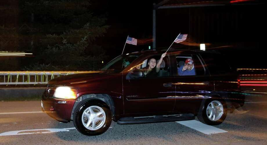 "People cheer and wave flags from a passing car on the ""Freedom Bridge"" just outside Joint Base Lewis-McChord, Sunday, May 1, 2011, near Tacoma, Wash., after they heard the news that Osama Bin Laden had been killed. Photo: AP"