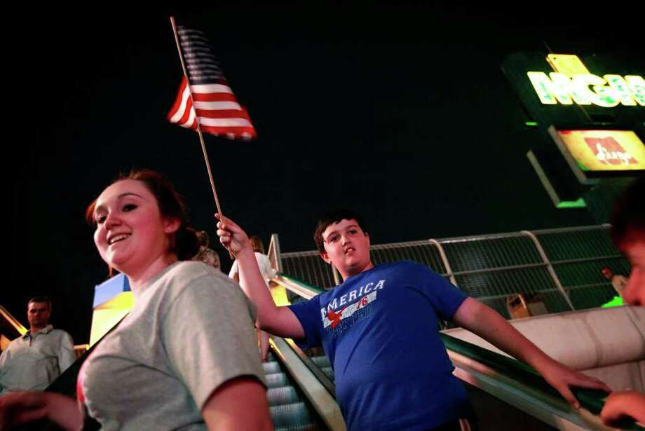Michael Truex, 12, of Henderson, Nev., waves an American flag outside of New York New York Hotel and Casino in reaction to news of Osama Bin Laden's death in Las Vegas on May 1, 2011. At left is sister Nicole Truex, 15. Their mother Terri, who served in the Navy, brought them down after hearing the news. Photo: AP