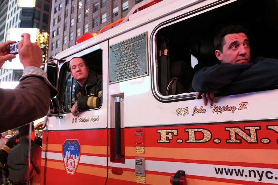 FDNY firefighter Scott Hickey, left, and a fellow firefighter who did not give his name, sit in a fire truck parked in New York's Times Square as a crowd gathers in reaction to the news of Osama Bin Laden's death early Monday morning May 2, 2011. A plaque with names of Ladder 4 firefighters who lost their lives in the Sept. 11 attacks, the house that Hickey belongs to, is seen on the side of the truck. Photo: AP