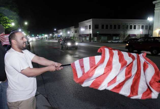Toufeq Ahmed waves a flag as he celebrates the news of the death of Osama Bin Laden in Dearborn, Mich., early Monday, May 2, 2011. President Barack Obama announced Sunday night, May 1, 2011, that Osama bin Laden was killed in an operation led by the United States. Photo: AP