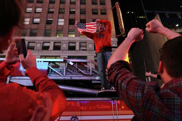 Dustin Fredrickson, of New York, center, holds up an American flag as he stands on a fire truck amongst those gathered in New York's Times Square reacting to the news of Osama Bin Laden's death early Monday morning May 2, 2011. Photo: AP