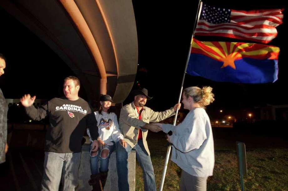 A small crowd starts to gather at the 911 Memorial in front of the Arizona State Capitol in Phoenix after President Barack Obama confirmed the death of Osama bin Laden in a late-night statement at the White House Sunday May 1, 2011.  Left to right, Hector Mejia, 18, of Tonopah, Ariz., Mark McDonald (cq) of Phoenix, Shonda Marek of Peoria, Ariz.,  John Dickson (cq) of Peoria, Ariz., and Shawna Sarraillon (cq) of Glendale, Ariz., give each other hand shakes. Photo: AP