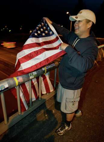 "U.S. Army Staff Sgt. Lemuel Nacionales, cheers and waves a U.S. flag on the ""Freedom Bridge"" just outside Joint Base Lewis-McChord, Sunday, May 1, 2011, near Tacoma, Wash., after he heard the news that Osama Bin Laden had been killed. Photo: AP"