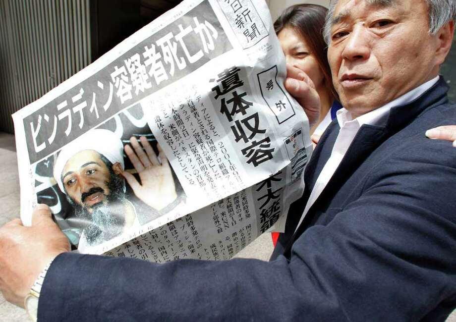 A man shows an extra edition of a Japanese newspaper in Tokyo Monday, May 2, 2011, reporting Osama bin Laden, the glowering mastermind behind the Sept. 11, 2001, terror attacks was killed in an operation led by U.S. forces. Japanese headlines read: Is Bin Laden dead?  His remains were taken custody, said President. Photo: AP