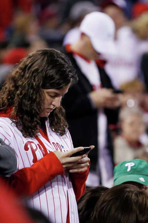 Fans check their cell phones during a baseball game between the Philadelphia Phillies and the New York Mets, Sunday, May 1, 2011, in Philadelphia. New York won 2-1 in 14 innings. News broke during the game that Osama bin Laden had been killed. Photo: AP