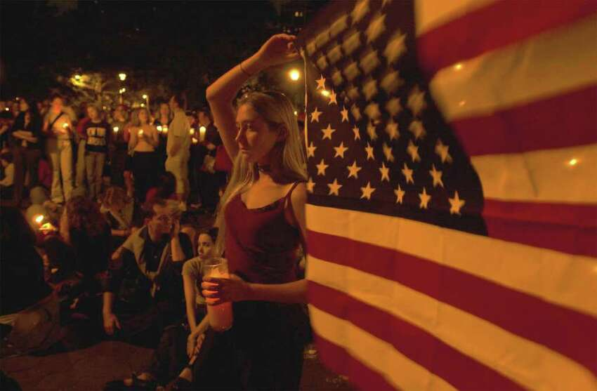 Drew Lehman holds an American flag and a candle during a candle light vigil held in Washington Square Park in New York Wednesday Sept. 12, 2001 for the victims of the World Trade Center Bombing.