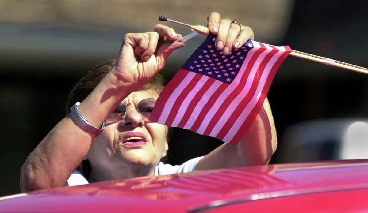 """Norma DeVito of Norwalk attaches an American flag to her car's antenna. """"I'm putting up the flag to show that I'm standing behind the country,"""" says DeVito. She purchased the flag at the Crossroads Variety on Connecticut Avenue."""