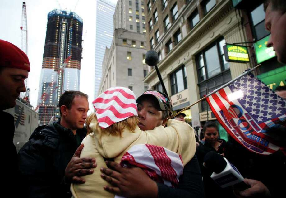 Stamford resident Dionne Layne, facing camera, hugs Mary Power as they react to the news of the death of Osama bin Laden in New York Monday. At left is 1 World Trade Center, also known as the Freedom Tower, which is under construction. Photo: Mark Lennihan, AP / AP2011