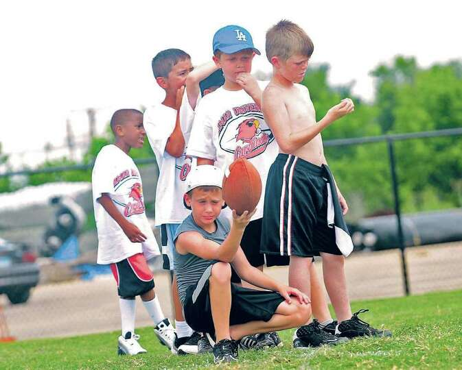 Kids wait in line before kicking practice during Lamar's football camp on Tuesday. The camp is run b