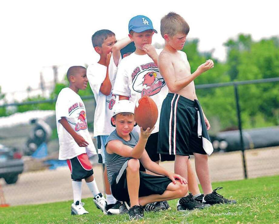 Kids wait in line before kicking practice during Lamar's football camp on Tuesday. The camp is run by Cardinal football coaches. Guiseppe Barranco/The Enterprise Photo: Guiseppe Barranco / Beaumont